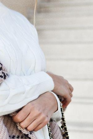 Nainen seisoo kädet ristissä vatsansa päällä.