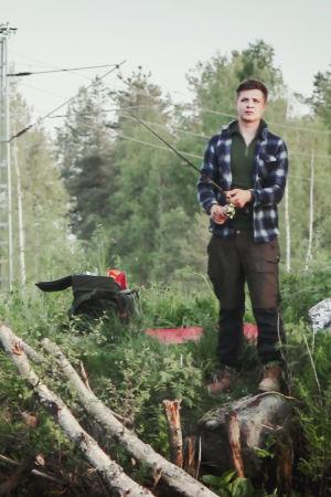 Ung man fiskar koncentrerat, håller i kastspö på grönskande åstrand.