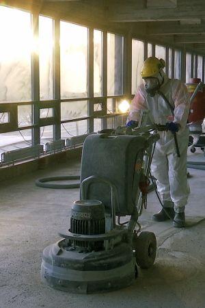 Mies poistaa asbestia rakennustyömaalla.