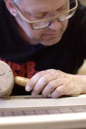 Jonni Roos rakentaa kitaraa, ja kovertaa taltalla ja vasaralla kitaran kaulaa.
