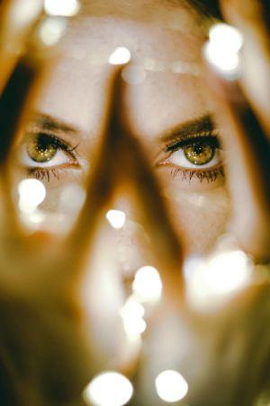 Nainen pitelee valoja käsissään.