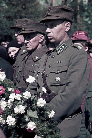 Sotilaita sankarihaudoilla kukkaseppeleet käsissään.