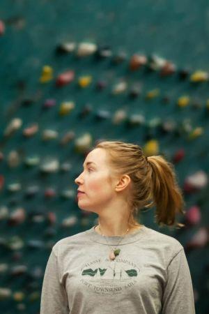 Eveliina Lempiäinen kiipeilyseinän edessä.