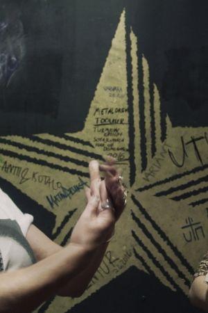 Kaksi naista seisoo mustan, kultaisella tähdellä koristellun seinän edessä. Toinen nainen irvistää toiselle.