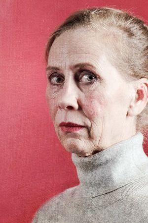 Kati Outinen eläytyy Helene Schjerfbeckin omakuvaan. Vakava nainen kuvattuna vahvan punaista taustaa vastaan.