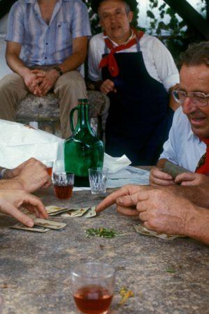 Baskimiehet pelaavat korttia baskerit päässä ja huivit kaulassa