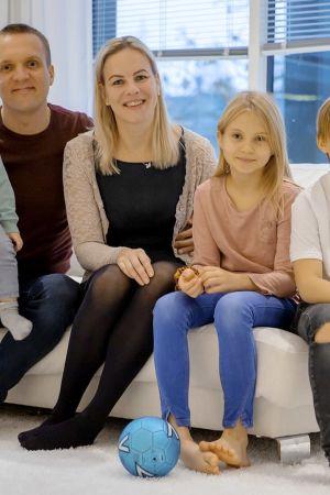 perhe vanhemmat ja lapset istuvat sohvalla iloisina