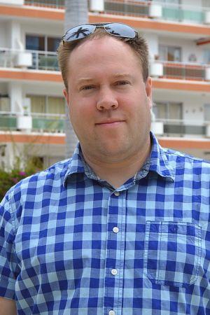 Nöjd Jonas Björkstrand står framför ett hotell