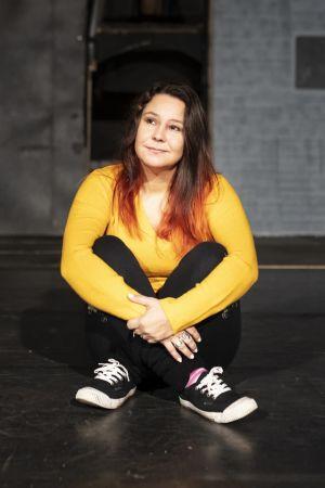 Anne Kassimäki istuu tyhjällä näyttämöllä.