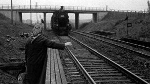 Nainen heilauttaa kättään junalle