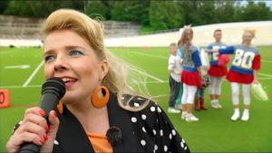 Susanna Vainiola juontaa lomamatkalaisten cheerleader-esityksen Velodromilla Helsingissä.