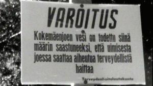 Kyltti Kokemäenjoen rannassa varoittaa vuonna 1969 Pori Jazzin yleisöä uimisesta saastuneessa vedessä.