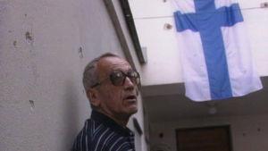 Osman Dikic seisoo kranaatti-iskuissa kärsineen Suomen konsulaatin edessä Sarajevossa vuonna 1994