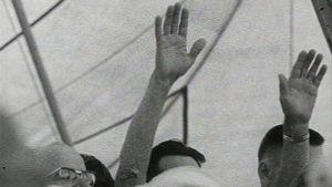 Mies nostaa kätensä ylös helluntailiikkeen kokouksessa