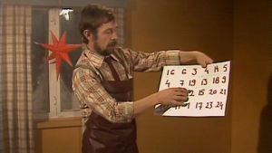 Mies askartelee joulukalenterin isälle.