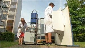 En forskarei vit rock kissar i ett litet bås medan en annan forskare håller uppe en slang ovanför ett glas. Slangen kommer från en stor maskin som förvandlar urin till dricksvatten.