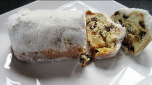 Stollen-kakku ja pari valmiiksi leikattua viipaletta valkoisella tarjoilulautasella.