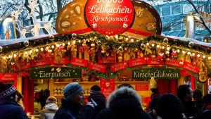 Joulukoristeltu herkkukoju Münchenin joulumarkkinoilla, ihmisiä kojun edessä.