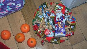 Puulattialla mandariineja sekä lautanen, jolla joulusuklaata, -makeisia ja maapähkinöitä kuorineen.