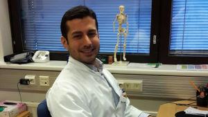 Mieslääkäri istuu työpöytänsä ääressä ja hymyilee kameralle.
