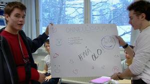 Oppilaat pitävät kylttiä kädessään