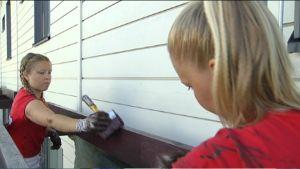 Två målare målar en pergola.