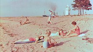 Auringonottajia rannalla vuonna 1961 valmistuneessa matkailufilmissä.