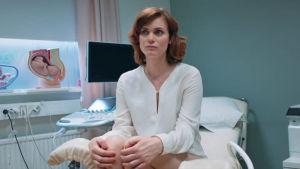 På bilden syns Liv Mjönes (Carro) sitta i en gynekologstol.