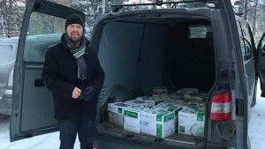 Kim Berg står framför paketbil med 18 lådor med namn.