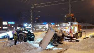 En plogbil har vält över tågräls. En man står bredvid och flera fordon försöker flytta den. Snö på marken.