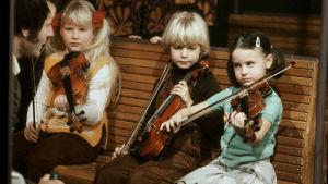Barn sitter på en bänk och spelar violin