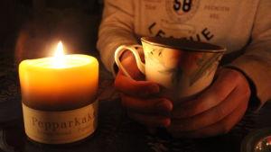 En kopp varm dryck och ett brinnande ljus.