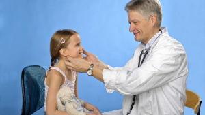 En läkare känner på en flickas hals.