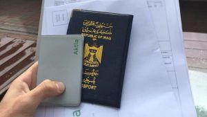 En hand håller i ett irakiskt pass samt papper från Aktiabanken. I bakgrunden syns bankkontoret.