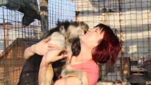 Salla Honkapää Glinan koiransuojelijoiden tarhalla Romaniassa. Sallalla on koira sylissään ja hän hymyilee.