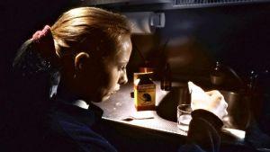 Kati Outinen sekoittaa myrkkyä lasiin. Kuva elokuvasta Tulitikkutehtaan tyttö.