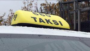 Taksi-kyltti auton katolla.