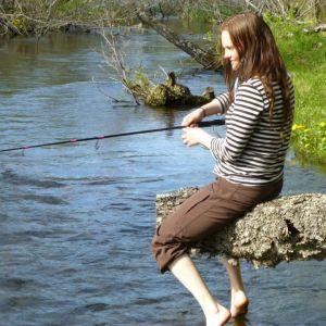 Suvi West istuu puun rungolla ja kalastaa. Kesäinen jokimaisema Saamenmaalta.