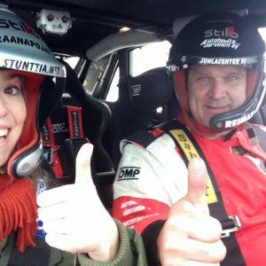 Stuntautokuljettaja Crazy Mike ja toimittaja Ida-Liina Huurtela istuvat auton sisällä ja tervehtivät kameraa.