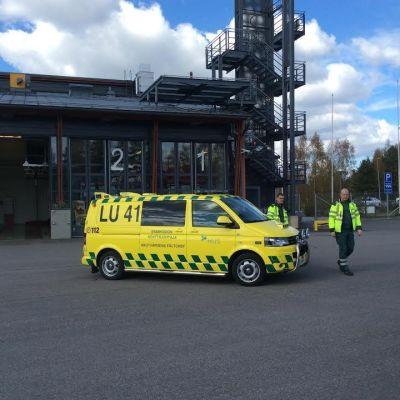 En gul fältchefsbil, liknar en ambulans. Två män i reflexrockar går bredvid bilen. I bakgrunden syns en brandstation.
