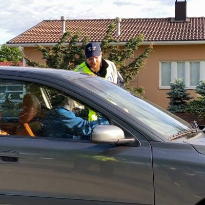 Poliisi puhalluttaa autoilijaa harmaassa autossa