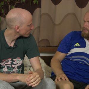 kaksi miestä keskustelevat kärkkäästi sohvalla
