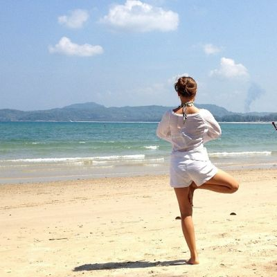 nainen tekee joogan tasapainoliikettä rannalla