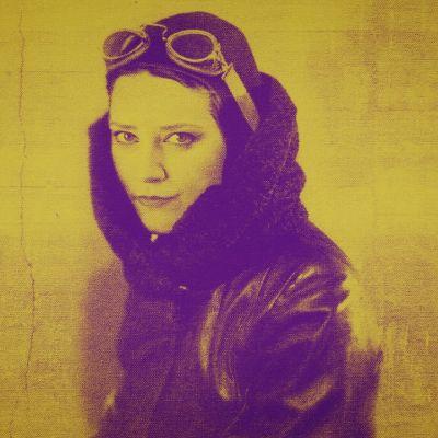 Naislentäjän violetti siluetti keltaisella taustalla. Naisella on päässään lentäjänlasit ja hän katsoo suoraan kameraan.