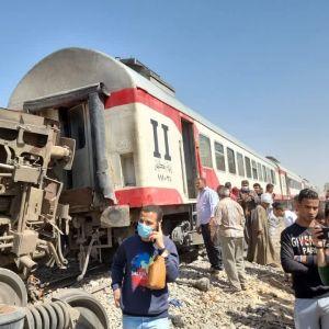 Kaksi junanvaunua, joista toinen on kaatunut, ja paljon ihmisiä