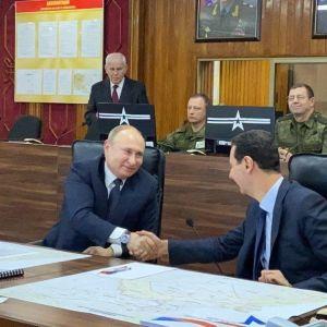 Vladimir Putin ja Bašar al-Assad kättelevät kokoussalissa, jossa istuu myös muita ihmisiä.