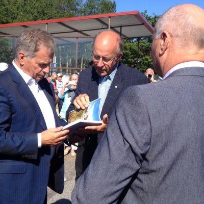 Hangon kaupunginhallituksen ja -valtuuston puheenjohtajat sekä kaupunginjohtaja tervehtivät Niinistöä Itäsatamassa.