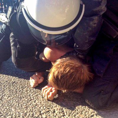 Mellakkapoliisi pidättää protestoijan.