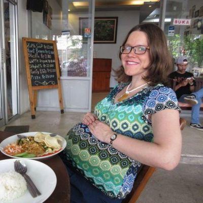 Nainen istuu ruokapöydän ääressä.