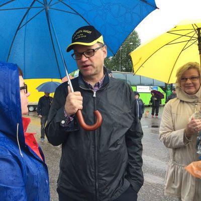 Juha Sipilä puhuu naisen kanssa.